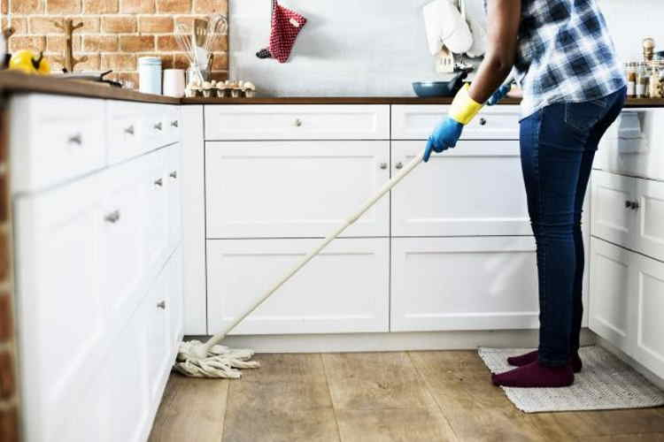 Woman mopping floor with everyday cleaning products that could harm your dog